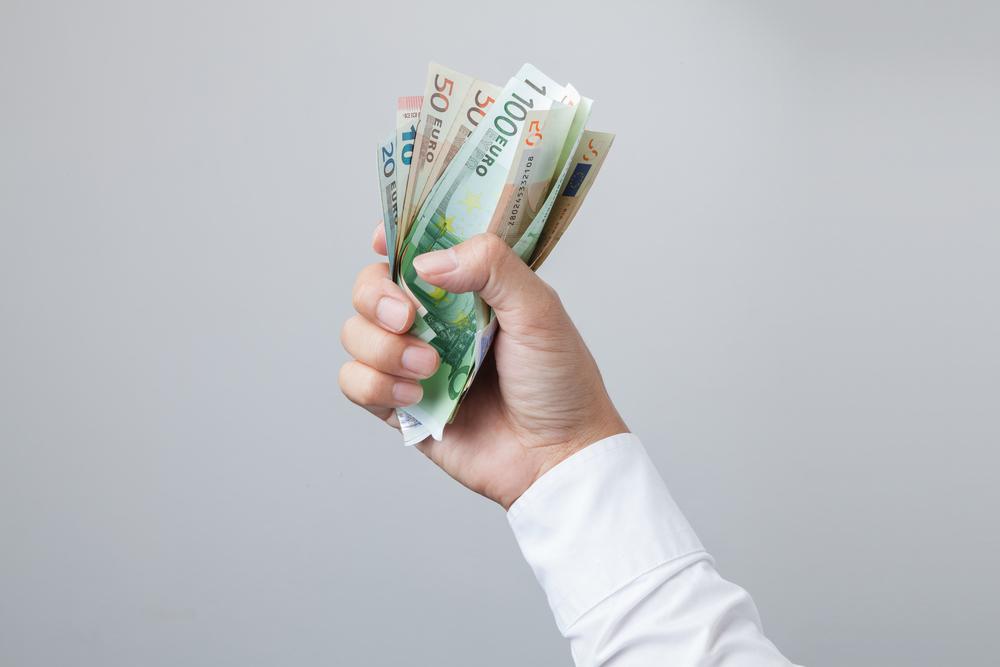 Mann hält Geldscheine in seiner Hand.